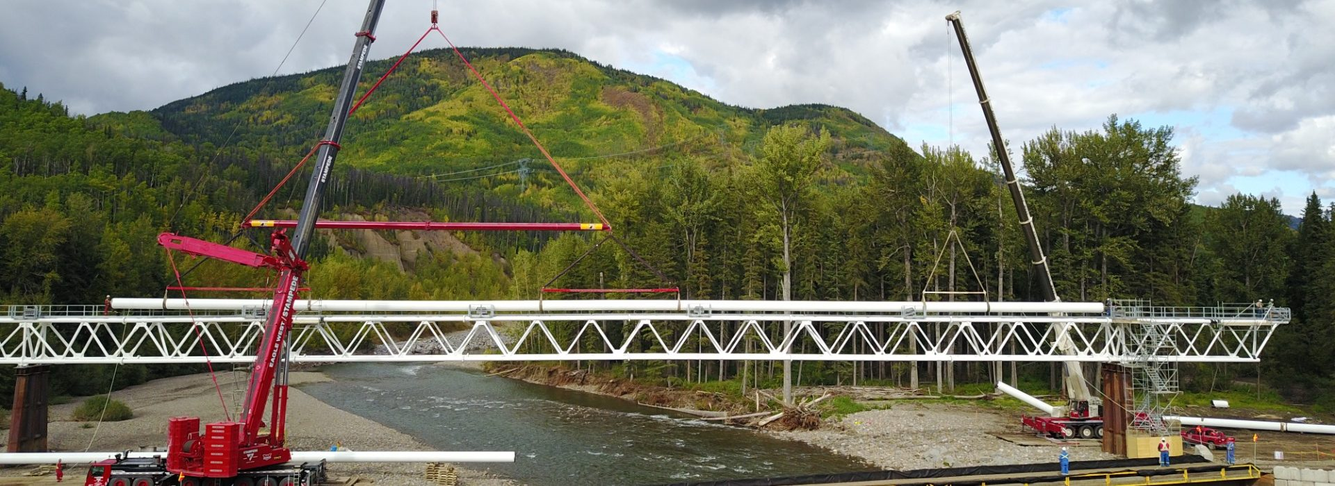 Triple J Pipelines constructing a large pipeline crossing over a river with cranes